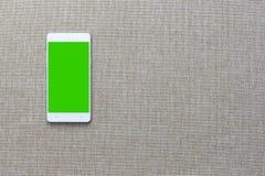Smartphone med på tygbakgrund, Greenscreen Arkivbild