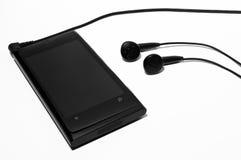 Smartphone med stereo- hörlurar Royaltyfria Foton