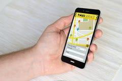 Smartphone med taxiapplikation på skärmen Fotografering för Bildbyråer