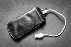 Smartphone med uppladdaren arkivbild