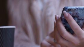 Smartphone-meisje die app op telefoon het drinken koffie gebruiken die in koffie glimlachen stock video