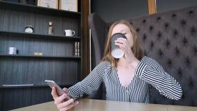 Smartphone-meisje die app op telefoon het drinken koffie gebruiken die in koffie glimlachen Mooie jonge toevallige vrouwelijke be stock videobeelden