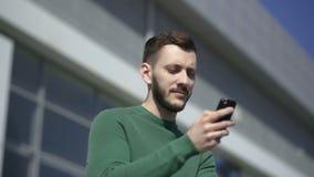 Smartphone-mens die mobiele celsmartphone in openlucht met behulp van stock videobeelden