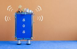 Smartphone with message SOS. Abstract robotic cellular phone on brown blue background need help. copy space.  stock image