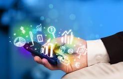 Smartphone met financiën en marktpictogrammen en symbolen Royalty-vrije Stock Foto