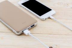 Smartphone met gouden machtsbank Royalty-vrije Stock Afbeeldingen