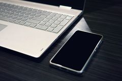 Smartphone met het exemplaar ruimtescherm en laptop op houten lijstachtergrond Het lege zwarte scherm van een mobiele linkerzijde stock afbeeldingen