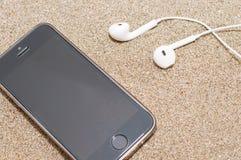 Smartphone met hoofdtelefoons op overzees zand Royalty-vrije Stock Afbeelding