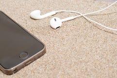 Smartphone met hoofdtelefoons op overzees zand Stock Afbeeldingen