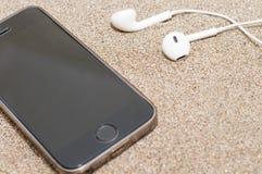 Smartphone met hoofdtelefoons op overzees zand Stock Foto's
