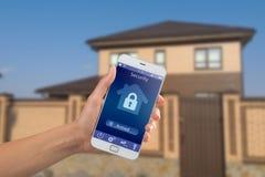 Smartphone met huisveiligheid app in een hand op de de bouwachtergrond stock fotografie