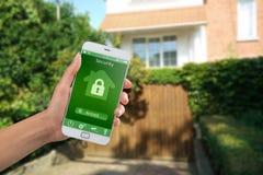 Smartphone met huisveiligheid app in een hand op de de bouwachtergrond stock afbeelding