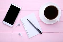 Smartphone met notitieboekje en kop van koffie op roze achtergrond stock afbeeldingen