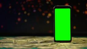 Smartphone mit Dollarbargeld, Lichter, die auf Hintergrund, on-line-Kasinospiel funkeln stock footage