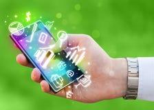 Smartphone mit Finanzierung und Marktikonen und -symbole Stockfoto