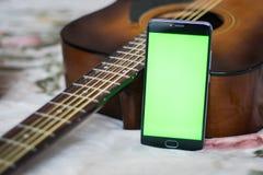 Smartphone mit grünem Schirm auf einer Akustikgitarre Lizenzfreies Stockfoto