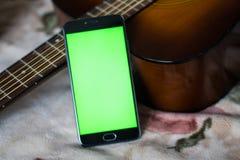 Smartphone mit grünem Schirm auf einer Akustikgitarre Stockfoto