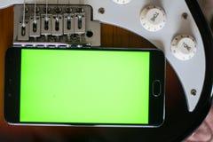 Smartphone mit grünem Schirm auf einer E-Gitarren-Gitarre Stockbild