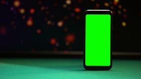 Smartphone mit grünem Schirm auf Schürhakentabelle, Lichter, die auf Hintergrund funkeln stock video