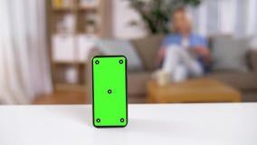 Smartphone mit grünem Schirm auf Tabelle zu Hause stock footage
