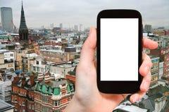 Smartphone mit herausgeschnittenem Schirm und London-Skylinen Lizenzfreies Stockfoto