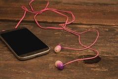 Smartphone mit Kopfhörern lizenzfreie stockbilder