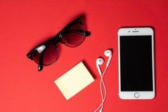 Smartphone mit leerem Bildschirm schlie?t an Kopfh?rer an gewundenes Kabel auf roter Hintergrund-Draufsicht, Sonnenbrille an stockbild