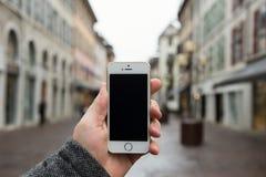 Smartphone mit lokalisiertem Schirm in den männlichen Händen Lizenzfreie Stockfotos