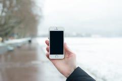 Smartphone mit lokalisiertem Schirm in den männlichen Händen Stockbild