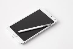 Smartphone mit Stift auf weißem Hintergrund Lizenzfreie Stockfotografie