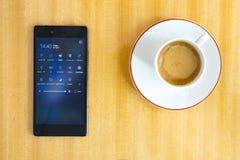 Smartphone mit Tasse Kaffee Stockfotos