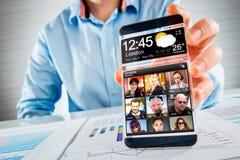 Smartphone mit transparentem Schirm in den menschlichen Händen. Stockbild