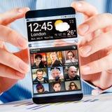 Smartphone mit transparentem Schirm in den menschlichen Händen. Stockfoto