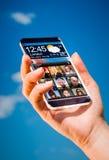 Smartphone mit transparentem Schirm in den menschlichen Händen Stockfoto