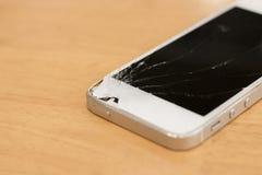 Smartphone mobiel met het Gebroken scherm op Achtergrondhout Stock Foto