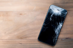 Smartphone mobile with a broken screen. Background wood stock photos