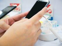 Smartphone mobile della tenuta della mano nel negozio del telefono cellulare Fotografia Stock