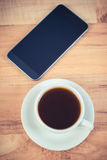 Smartphone, mobile phone with blank screen and cup of coffee. Vintage photo, Mobile phone with blank screen, smartphone and relax with black coffee Royalty Free Stock Image