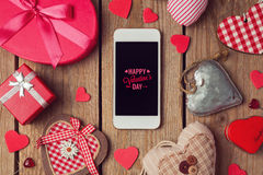 Smartphone mock up template for Valentine's day with heart shapes. Over wooden table Royalty Free Stock Photography