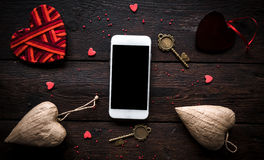 Smartphone mock Valentine`s day. Concept on wooden background Stock Images