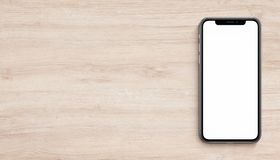 Smartphone mockup similar to iPhone X flat lay top view lying on wooden office desk banner with copy space. Smartphone mockup similar to iPhone X lying on wooden stock images