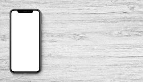 Smartphone similar to iPhone X mockup flat lay top view lying on wooden office desk banner with copy space. Smartphone similar to iPhone X mockup lying on wooden royalty free stock images
