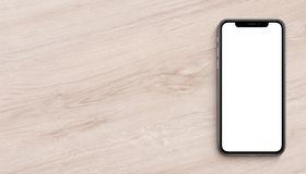 Smartphone similar to iPhone X mockup flat lay top view lying on wooden office desk banner with copy space stock photo