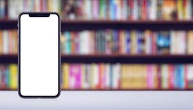 Smartphone mockup similar to iPhone X front and back sides on the desk in book store banner with copy space. Smartphone mockup similar to iPhone X front and back stock image
