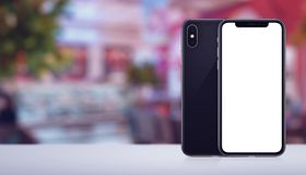 Smartphone mockup similar to iPhone X front and back sides on the desk in cafe banner with copy space. Smartphone mockup similar to iPhone X front and back sides stock photos