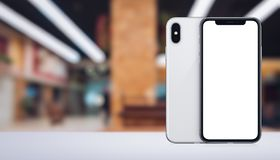 Smartphone similar to iPhone X mockup front and back sides on the desk in office space banner with copy space. Smartphone similar to iPhone X mockup front and royalty free stock photography