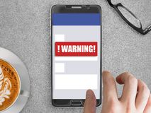 Mobile phone with red warning notification. Smartphone mockup with red warning notification on screen with finger touching Stock Image