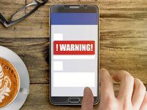 Mobile phone with red warning notification. Smartphone mockup with red warning notification on screen with finger touching Royalty Free Stock Photo