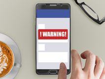 Mobile phone with red warning notification. Smartphone mockup with red warning notification on screen with finger touching Royalty Free Stock Image