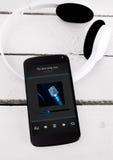 Smartphone moderno en el tablero de madera con los auriculares del bluetooth Imágenes de archivo libres de regalías